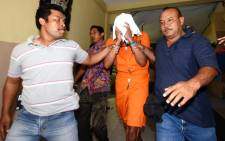 Police escort suspect Tommy Schaffer (C), suspected in the murder of Sheila von Wiese Mack, while in custody at Bali police hospital in Denpasar on the Indonesian resort island of Bali on 15 August 2014. Picture: AFP.