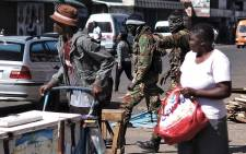 FILE: Two Zimbabwean soldiers wearing balaclavas shout orders to street vendors and money changers in the Copacabana market in Harare, on 2 August 2018. Picture: AFP