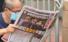 This file photo taken on 19 June 2021 shows a supporter reading a copy of the 'Apple Daily' newspaper outside a court in Hong Kong, after the two Apple employees were charged with collusion over their newspaper's coverage after authorities deployed a sweeping security law.  Picture: Peter Parks/AFP