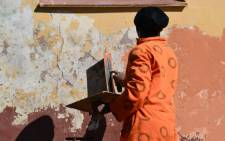 A prisoner from East London plasters the wall at Qunu Junior Secondary School in honour of Nelson Mandela's birthday on 18 July 2012. Picture: Aletta Gardner/EWN