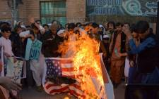 Pakistani supporters of the Jamaat-ud-Dawa (JuD) organisation burn Indian (R) and US flags during a protest after JuD leader, Hafiz Saeed was placed under house arrest by authorities in Quetta on 31 January 2017. Picture: AFP.
