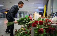 This handout picture taken and released by the Ukrainian presidential press service shows Ukraine's President Volodymyr Zelensky placing flowers at a memorial for the victims of the Ukraine International Airlines Boeing 737-800 crash in the Iranian capital Tehran, at the Boryspil airport outside Kiev on 9 January 2020. Picture: AFP