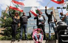People gather and wave Lebanon national flags in front of the UN-backed Special Tribunal for Lebanon (STL) at Leidschendam in the Netherlands on 18 August 2020. Picture: AFP