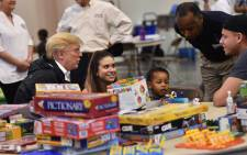 US President Donald Trump, with Secretary of Housing and Urban Development Ben Carson (2nd R), visits Hurricane Harvey victims at NRG Center in Houston on 2 September 2017. Picture: AFP.