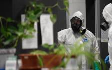 Members of the Spanish Military Emergencies Unit (UME) wearing protective gear prepare to disinfect the Lope de Vega Cultural Center in the Vallecas neighbourhood where rapid antigen test for COVID-19 were conducted to residents of the area, on 30 September 2020 in Madrid. Picture: AFP