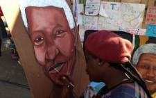 A painter with one of his drawings of the Iconic former statement Nelson Mandela. Picture:Sebabatso Mosamo/EWN.