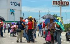People queue up outside a supermarket in Valencia, 180 km west of Caracas on 11 August 2015. Picture: AFP.