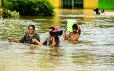 Residents walk through floodwaters as they evacuate to a safer place in Kabacan, North Cotabato, on the southern island of Mindanao in the Philippines on 23 December, 2017. Picture: AFP