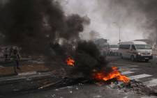 A taxi tries to make its way through the barricade of burning tires and rubble. Khayelitsha residents protested over high water bills. Picture: Bertram Malgas