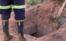 FILE: A rescue worker stands next to the illegal mine shaft where eleven miners were rescued after being trapped underground for almost a day on 16 February 2014. Picture: Reinart Toerien/EWN