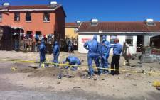 Police forensic experts in Hazmat suits digging a deep hole behind the homes of two missing Mitchells Plain girls. Picture:EWN