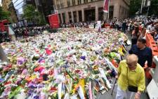 Visitors walk past flowers at a makeshift memorial near the scene of a fatal siege in the heart of Sydney's financial district on 17 December, 2014. Picture: AFP.