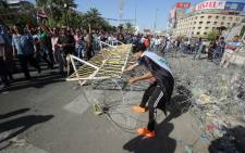 """A supporter of Iraqi cleric Moqtada al-Sadr removes barbed wire as demonstrators make their way towards Baghdad's fortified """"Green Zone"""" on 20 May 2016. Picture: Ahmad al-Rubaye/AFP."""
