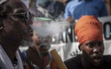 Rastafarians smoke cannabis outside the South African Constitutional Court before the ruling on the private use marijuana is delivered. Picture: Thomas Holder/EWN