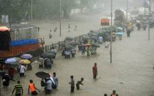 FILE: Mumbai residents wade through a flooded street during heavy rain showers on 29 August 2017. Picture: AFP.