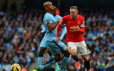 Manchester United's English striker Wayne Rooney (R) goes round Manchester City's Belgian defender Vincent Kompany (L) during the English Premier League football match between Manchester City and Manchester United. Picture: AFP.