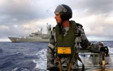Authorities search for debris on a rigid hull inflatable boat as HMAS Perth searches for missing Malaysia Airlines flight MH370 in the southern Indian Ocean. Picture: AFP.