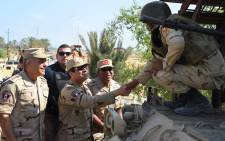 A handout picture released by the Egyptian Presidency on 4 July, 2015, shows Egyptian President Abdel Fattah al-Sisi (C) shaking hands with a member of the security forces during a visit to the Sinai Peninsula following a wave of deadly attacks on armed forces by the Islamic State jihadists. Picture: AFP.