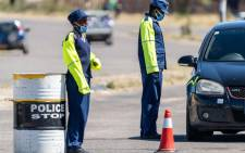 FILE: Police officers manning a check point quiz a driver going into the central business district on 20 April 2020, in Emakhandeni township, Bulawayo, Zimbabwe. Picture: AFP.