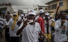 A crowd campaigns under a downpour for a candidate to the Congolese parliament, Christian Ngelebeya Papy, on 17 December 2018, in Kinshasa. Democratic Republic of Congo. Picture: AFP.