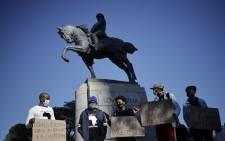 FILE: Demonstrators stand next to the statue of Louis Botha on horseback, the first prime minister of the Union of South Africa, during a demonstration calling for the removal of the statue in front of the South African Parliament, in Cape Town on 16 June 2020. Picture: AFP