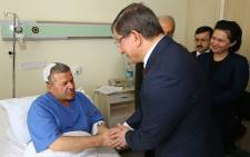 Turkish Prime Minister Ahmet Davutoglu, (2nd-R), talking to a wounded man at Ankara, during a visit at the hospital after a massive car bomb that struck five buses carrying military service personnel. Picture: AFP