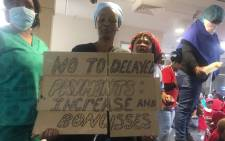 FILE: One of the protesters holding a placard during demonstrations over wages at the Charlotte Maxeke Academic Hospital in Johannesburg on 31 May 2018. Picture: Christa Eybers/EWN.