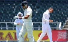 SOUTH AFRICA, Johannesburg : Indian batsman Virat Kohli (L) walks off the field after being dismissed by South African bowler JP Duminy (R) on the fourth day of the first cricket Test between South Africa and India at the Wanderers Stadium in Johannesburg on December 21, 2013. AFP PHOTO
