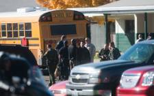 Law enforcement officers gather in the parking lot after a shooting at Sparks Middle School 21 October, 2013 in Sparks, Nevada. A staff member was killed and two students injured after a student opened fire at the school. Picture: AFP.