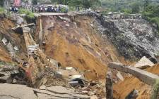 FILE: A road surface swept away by a landslide caused by torrential overnight rains is photographed in the Lemba district of Kinshasa, on 26 November 2019. Picture: AFP