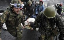 Protesters carry a wounded protester during clashes with police, after gaining new positions near the Independence square in Kiev on 20 February, 2014. Picture: AFP.