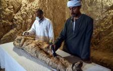 Egyptian archaeological technicians restore a mummy wrapped in linen, found at the newly discovered 'Kampp 150' tomb at Draa Abul Naga necropolis on the west Nile bank of the southern Egyptian city of Luxor, on December 9, 2017. Picture: AFP