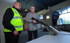 This photo taken on 4 July 2019 shows New Zealand police officers handling a gun example at a press preview ahead of a gun buyback scheme at the Trentham racecourse in Upper Hutt, near Wellington. Picture: AFP