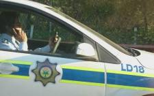 A police officer using two cellphones on Barry Hertzog Drive in Johannesburg. Picture: Twitter @Schmidt.
