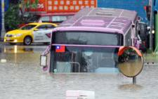 A bus sits half submerged on a flooded road in New Taipei City on August 2, 2012, as Typhoon Saola pounds Taiwan. Picture: AFP.