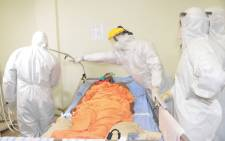 FILE: Medical staff wearing personal protective equipment tend to a COVID-19 coronavirus patient in the infectious diseases department at the Donka hospital in Conakry, Guinea, on 13 May 2020. Picture: AFP