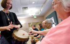 In this file photo music therapist Heather Davidson (L) plays a drum with Claire Diering (R) during a drum circle with patients with Alzheimer's disease at the Copper Ridge Care Center in Sykesville, Maryland, on October 23, 2009. The United States on 7 June 2021 approved a drug called Aduhelm to treat patients with Alzheimer's, the first new medicine against the disease in almost two decades and the first to address cognitive decline linked to the condition. Picture: AFP