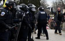 Trump supporters face off with police and security forces in front of the US Capitol in Washington DC on 6 January 2021. Donald Trump's supporters stormed a session of Congress to certify Joe Biden's election win. Picture: AFP.