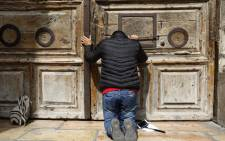 A pilgrim prays outside the closed gate of the Church of the Holy Sepulchre in Jerusalem's Old City on 25 February 2018. Picture: AFP