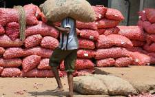 FILE: An Indian labourer carries a sack of onions at the Agricultural Produce Market Committee yard in Bangalore. Picture: AFP.