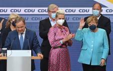German Chancellor Angela Merkel (R) waves on stage as leader of Germany's conservative Christian Democratic Union (CDU) party and candidate for Chancellor Armin Laschet (L) speaks on stage at the CDU headquarters after the estimates were broadcast on television in Berlin on 26 September 2021 after the German general elections. Picture: John MACDOUGALL/AFP