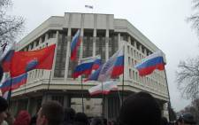 Pro-Russian protesters hold Russian flags as they rally in front of the Crimean parliament in Simferopol on 27 February, 2014. Picture: AFP.