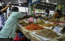 A vendor (R) sells dried fish at a market in Colombo on 28 August 2021 after Sri Lanka extended a stringent coronavirus curfew for another week after reporting its highest daily death toll of more than 200. Picture: ISHARA S. KODIKARA/AFP