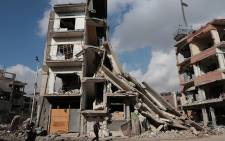 Syrians walk past a destroyed building in the rebel-held town of Douma, on the eastern outskirts of Damascus, on December 30, 2016, on the first day of a nationwide truce. Clashes erupted between Syrian government forces and opposition fighters in an area outside Damascus, despite a nationwide truce that began at midnight, a monitor said. Picture: AFP.