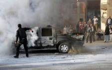FILE: An Egyptian policeman tries to extinguish a police vehicle set on fire by Muslim Brotherhood supporters on a ring road in the capital, Cairo. Picture: AFP.