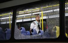 The damages to the windows of an Olympic journalists bus hit while driving on the Transolympica Highway are inspected by an official in Rio de Janeiro on August 9, 2016. Picture: AFP