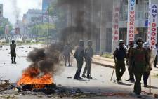 Police officers pass burning tyres on 6 June, 2016 in Kisumu, during demonstrations led by Coalition for Reforms and Democracy opposition party leader Raila Odinga, demanding the national electoral oversight body, the Independent Electoral and Boundaries Commission (IEBC), disband the electoral body. Picture: AFP.