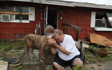 "Steve Culver cries with his dog Otis as he talks about what he said was the, ""most terrifying event in his life,"" when Hurricane Harvey blew in and destroyed most of his home while he and his wife took shelter there on 26 August, 2017 in Rockport, Texas. Picture: AFP."