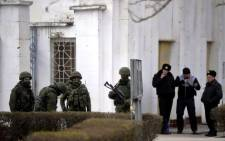 Ukrainian officers (R) stand outside the Ukrainian navy south headquarters base in Novoozerne next to a group of Russian soldiers after the base was taken over by Russian forces on 19 March.Picture:AFP.