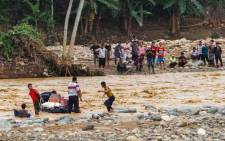 FILE: Villagers use inflated inner tyre tubes to deliver supplies across a river at the Banjar Irigasi village in Lebak, Banten province, in Indonesia on 2 January 2020, after flooding triggered by heavy rain hit the area. Picture: AFP